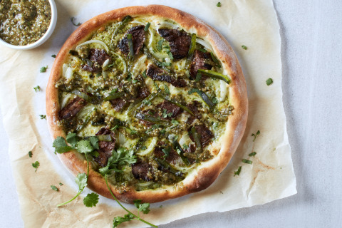 California Pizza Kitchen fan-favorite Carne Asada Pizza is back for National Pizza Month! Featuring fire-roasted poblanos, tender marinated steak, Monterey Jack and Mozzarella cheeses, yellow onions and fresh cilantro pesto, served with a side of housemade salsa verde. (Photo: California Pizza Kitchen)