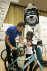 UnitedHealthcare Pro Cycling Team member Chris Jones gives a bike helmet and bicycle to Ja'niya Dossman, 7, at the Edward Kemble Elementary School branch of the Boys & Girls Clubs of Greater Sacramento (Photo: Gary Fong).