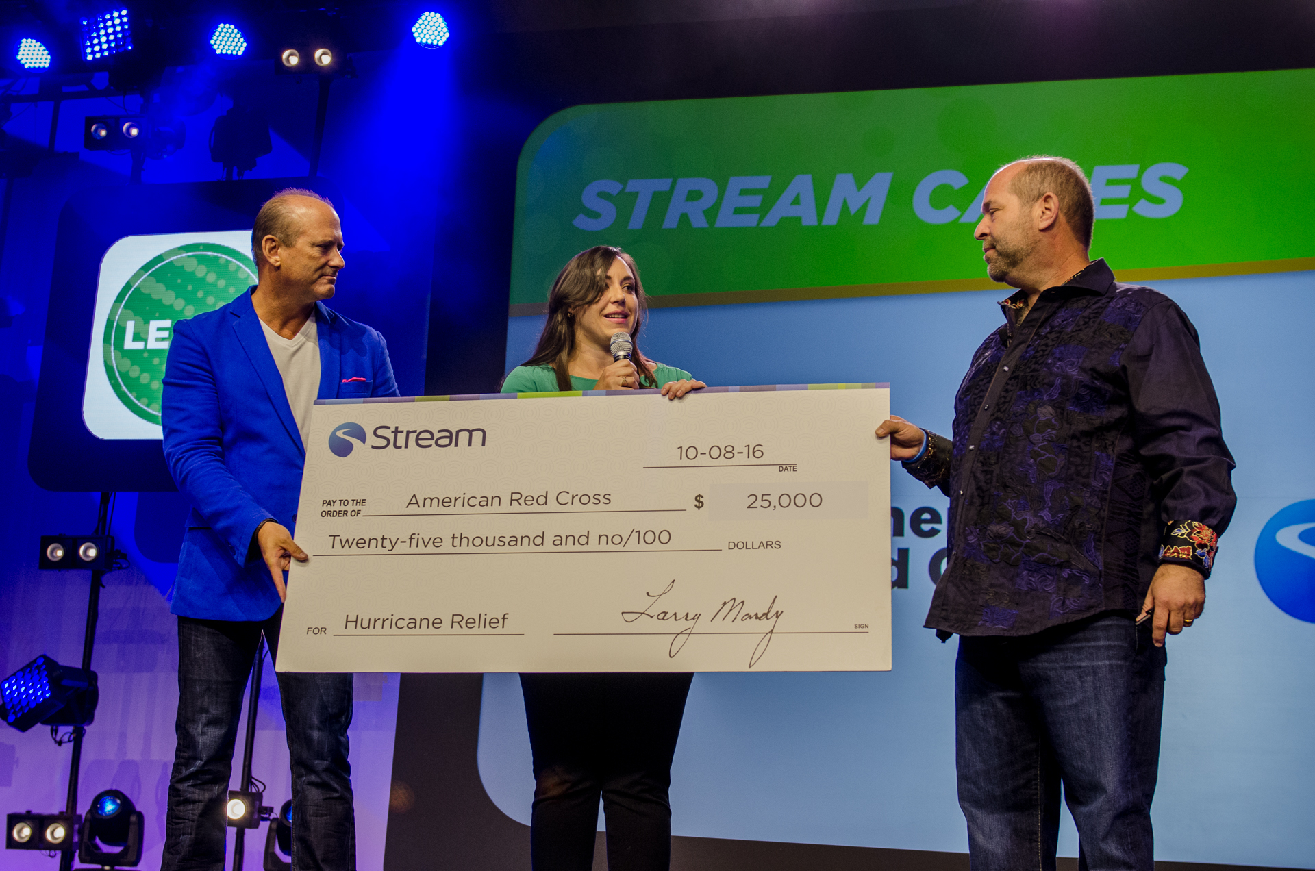 Larry Mondry and Dan O'Malley of Stream present Natalie Valenti Butters of the American Red Cross North Texas Region with Stream's donation. (Photo: Business Wire)