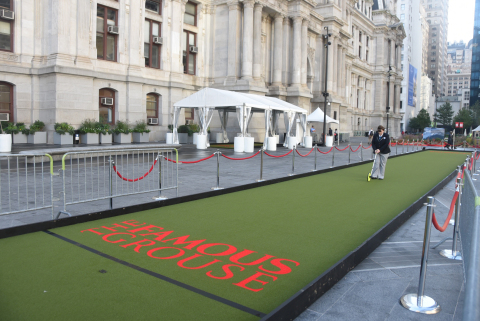 Christina Flounders-Conlon, an adjudicator for Guinness World Records, measures out a putting green at Dilworth Park at City Hall, Philadelphia, PA on Tuesday morning to verify its length at 104 feet, 2 inches, which, when played on later by former Phila. Eagle Hollis Thomas, became the world record holder for longest putting green. A five-hole miniature golf course was part of the day-long event sponsored by The Famous Grouse, Scotland's number one scotch whiskey. (Photo: Curt Hudson)