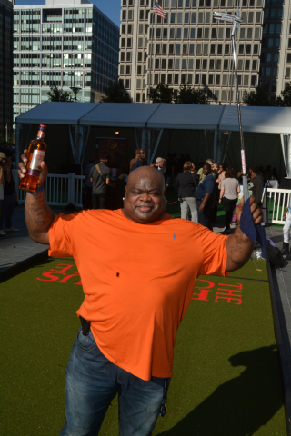 """Former Eagle Hollis Thomas celebrates helping set a Guinness World Record at an event to establish """"the world's largest putting green"""" at Dilworth Park at City Hall Tuesday. The 104 foot and 2 inch putting green  installed at Dilworth became certified as the world's longest by a representative of the Guinness Book of World Records. The event was sponsored by The Famous Grouse, Scotland's number one Scotch. (Photo: Mark C. Psoras)"""