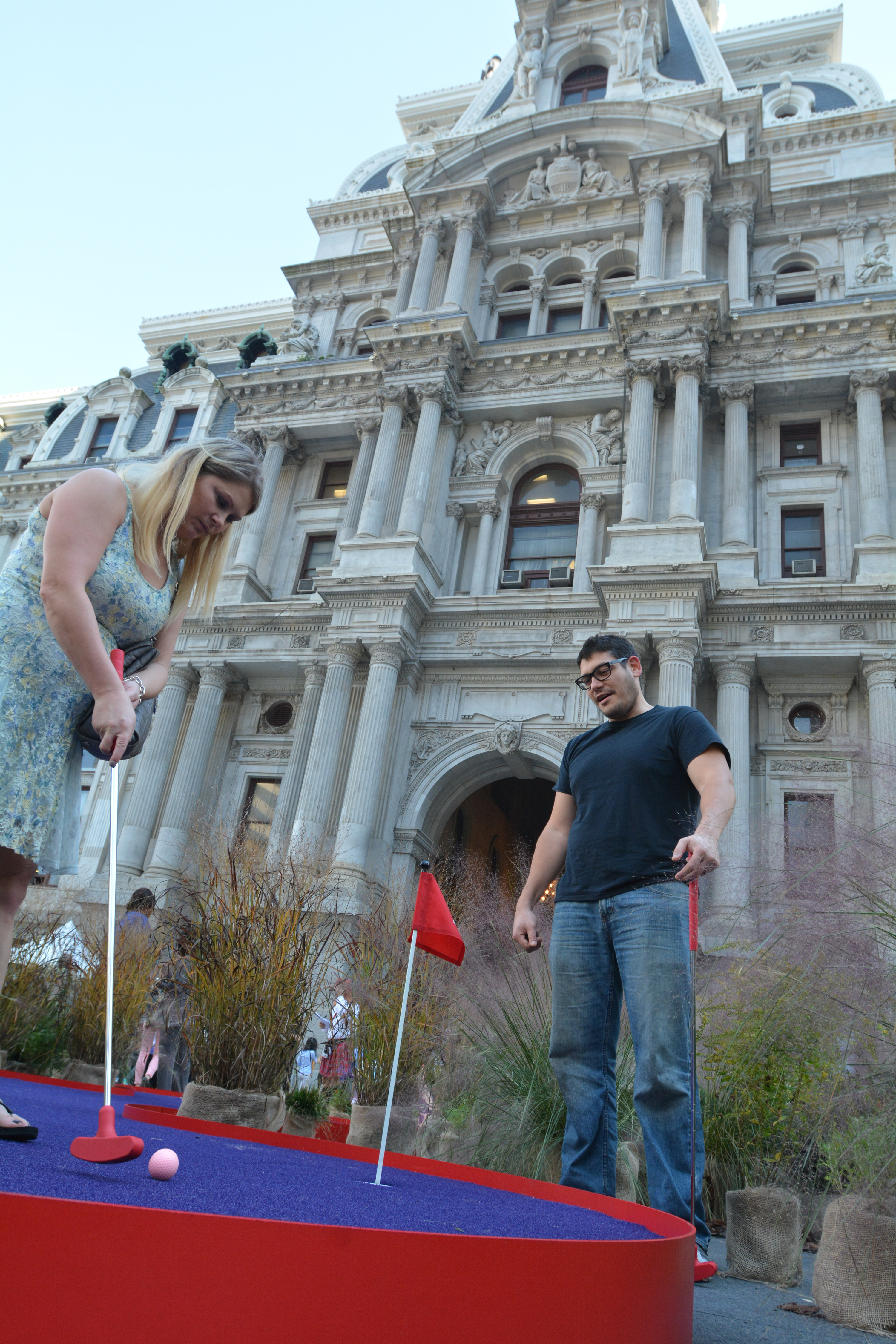 """A couple plays a round of miniature golf on a five-hole course set up as part of """"the world's largest putting green"""" event at Dilworth Park at City Hall Tuesday. A 104-foot 2-inch putting green  at Dilworth at which former Eagle Hollis Thomas helped set a Guinness World Record was part of the event. The event was sponsored by The Famous Grouse, Scotland's number one Scotch. (Photo: Mark C. Psoras)"""