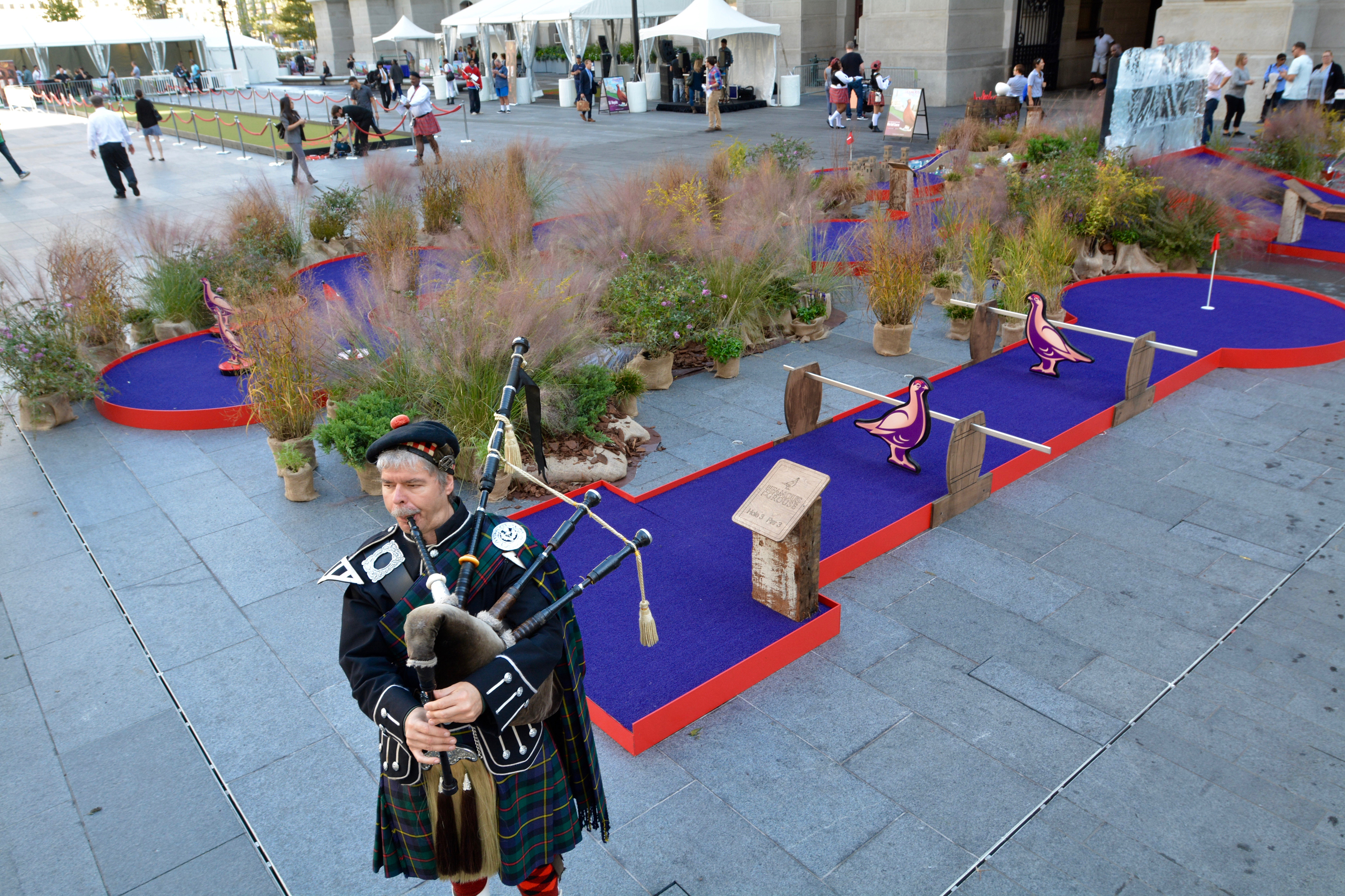 """Bagpiper Charles Rutan of Philadelphia plays the pipes next to a miniature golf course set up as part of """"the world's largest putting green"""" event at Dilworth Park at City Hall Tuesday. A 104 foot and 2 inch putting green  at Dilworth at which former Eagle Hollis Thomas helped set a Guinness World Record was part of the event. The event was sponsored by The Famous Grouse, Scotland's number one Scotch. (Photo: Mark C. Psoras)"""
