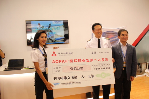 "Julie Wang (Wang Zheng) receiving AOPA China's 1,000,000 Yuan Ren'min'bi ""prize"" for being the first Chinese woman to fly around the world from AOPA China Secretary General Zhang Feng at the Zhuhai Airshow (Photo: Business Wire)"