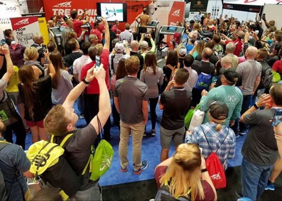 A huge crowd of fellow runners gathers at The Running Event, a trade show for run specialty retailers, to watch Altra athlete Jacob Puzey break the world record for fastest 50-miler on a treadmill. Puzey is at the very top center of the photo, shirtless, on the treadmill. (Photo: Altra)