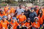 "San Diego Chargers running back and Rally Health Ambassador Melvin Gordon and Rally Health hosted a ""Holiday Bike Build"" today for children of service members stationed at Naval Base San Diego. The event, which showcased simple steps families can take to live healthier lives, gave 52 children the opportunity to ""trick out"" brand new Diamondback bikes that they got to take home. Here, Gordon and David Ko, President and COO of Rally Health, pose with a group of children on their new bikes. (Photo: Rally Health)"