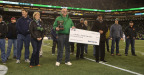 Tumwater High School's Sid Otton is presented with the Seahawks Coach of the Year award by Seattle Seahawks Director of Youth Football and Legends Projects Paul Johns, and UnitedHealthcare Pacific Northwest CEO Claire Verity during a pregame ceremony at the Seahawks vs. Rams game Dec. 15 at CenturyLink Field (Photo courtesy of Seattle Seahawks).