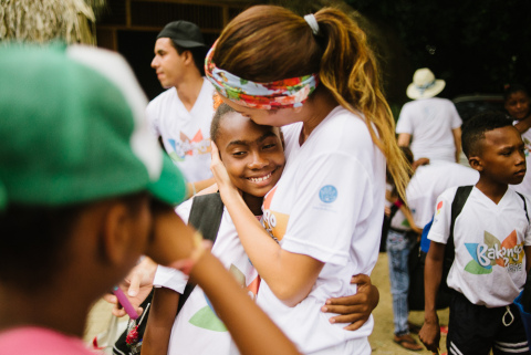 A counselor hugging a camper at the end of their immersive peace and reconciliation experience at Ca ...