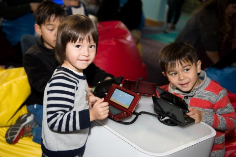 In this photo provided by Nintendo of America, kids and parents gather at TeenScape in Los Angeles Public Library's Central Library location in Downtown Los Angeles to attend a workshop where they learned the basics of video game course design using Super Mario Maker for Nintendo 3DS. With the help of Nintendo experts, attendees designed and played through their own Super Mario-themed courses by highlighting the creative tools available within the Super Mario Maker for Nintendo 3DS game.
