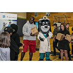 """Cindy Spain, RN, Vice President of Health Services, UnitedHealthcare Community Plan; UnitedHealthcare mascot Dr. Health E. Hound; Rees Odhiambo, Seattle Seahawks Guard; and Nancy Giunto, Executive Director, Washington Health Alliance passed out 150 NERF ENERGY Game Kits to members of the Boys & Girls Clubs of King County this morning. The local youth were led through exercises and relays to test out their new NERF ENERGY Game Kit that tracks activity earning """"energy points"""" in order to play the game. The donation is part of a recently launched national initiative and collaboration between Hasbro and UnitedHealthcare, featuring Hasbro's NERF products that encourages young people to become more active through """"exergaming."""" L to R: Odhiambo, Dr. Health E. Hound, Spain (Photo: Kim Doyel)."""