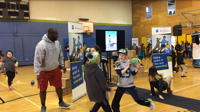 "Members of the Boys & Girls Clubs of King County participate in exercises and relays with UnitedHealthcare mascot Dr. Health E. Hound and Rees Odhiambo, Seattle Seahawks Guard, while wearing NERF ENERGY activity bands. Nearly 150 Wallingford Club members received NERF Energy Game Kits from Hasbro and UnitedHealthcare to encourage greater physical activity. The donation is part of a recently launched national initiative and collaboration between Hasbro and UnitedHealthcare, featuring Hasbro's NERF products that encourages young people to become more active through ""exergaming"" (Video: Anita Sen)."