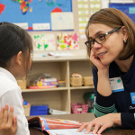 Schwab employee Elinore Robey provides a lesson in saving to a Garfield Elementary School student in Oakland, California.(Photo: Business Wire)