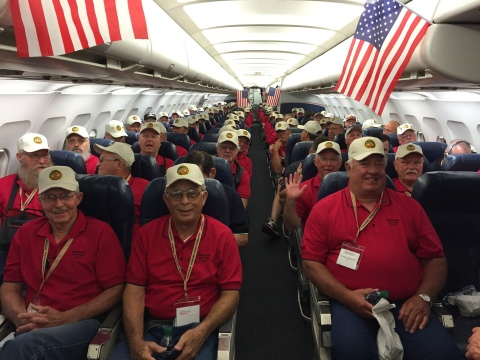 """Pictured is one of three planes from the Vietnam Veterans Flight on June 6, 2016, to support 500 veterans from Nebraska with their visit to the Vietnam Veterans Memorial in Washington D.C. Veterans wore red, white or blue shirts to reflect their plane assignment for the event. JQH's Embassy Suites by Hilton Omaha - La Vista Hotel & Conference Center in Nebraska is pleased to continue collaborating with Omaha-based non-profit Patriotic Productions to support veterans initiatives, including the Vietnam Veterans Flight - 2017: """"The Final Mission"""" and the """"Remembering Our Fallen"""" memorial. Photo Source: Patriotic Productions"""