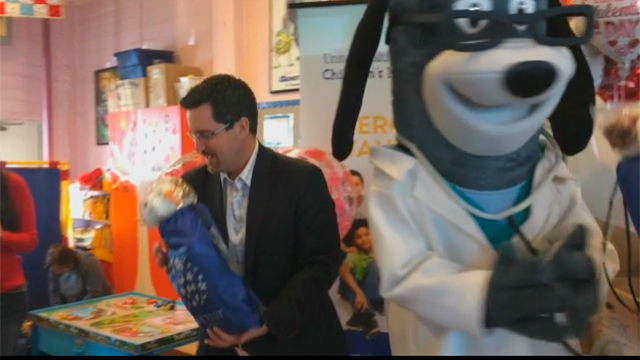 Local children receive a Valentine's Day-themed Grins 2 Go™ bag from Kevin Kandalaft of UnitedHealthcare at Wellspring Women's Center on Monday, Feb. 13. Wellspring serves as a drop-in center to women and their children, providing food and social services in a safe and enriching environment (Video: Anita Sen).