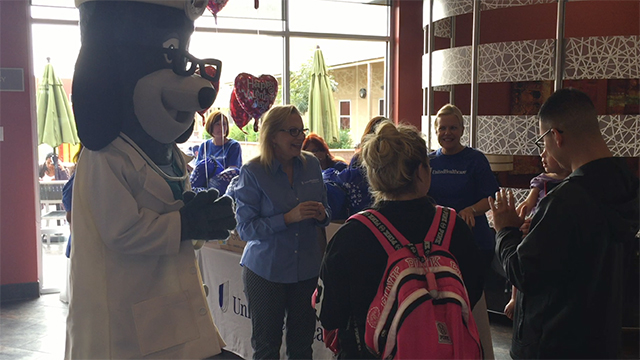 "Melissa Stout-Penn of UnitedHealthcare and mascot Dr. Health E. Hound give a Grins to Go bag to a family at Ronald McDonald House Charities of San Diego Tuesday. UnitedHealthcare employees distributed 150 of the Valentine's Day-themed bags to families at the organization. Ronald McDonald House provides a ""home away from home"" for families with children being treated for serious, often life-threatening conditions at local hospitals (Video: Matt Rodriguez)."