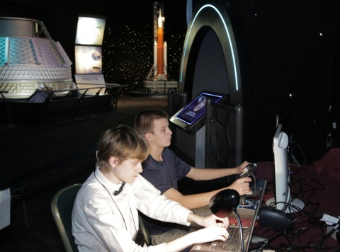 Trent Walker (left) and Justin Golabek simulate the landing of a Space Shuttle at Kennedy Space Center as part of the Student Astronaut Challenge at the KSC Visitors Center Feb. 16. The students were part of a team from St. John Paul II Catholic High School in Tallahassee, Florida, which was sponsored by Harris Corporation. The team was among 15 finalists to take part in the high school division of the competition that promotes Science, Technology, Engineering and Mathematics (STEM) education. (Photo: Business Wire)