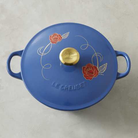 """The Beauty and the Beast Soup Pot by Le Creuset is made in France, features a hand-applied red rose-and-vine appliqué design on lid and a stainless-steel knob with gold metallic finish engraved with """"Be Our Guest."""" (Photo: Business Wire)"""