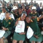Young girls pose with their free sanitary pads and school supplies. (Photo: Business Wire)