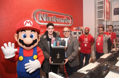 In this photo provided by Nintendo of America, Captain Nintendo makes the very first Nintendo NY store in-store purchase of the Nintendo Switch system from Doug Bowser, Senior Vice President Sales and Marketing, at the Nintendo NY store on March 3. (Photo: Nintendo of America)
