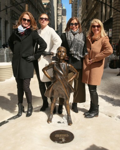 """ascena Board Members Katie Bayne, Senior Vice President, Global Sparkling Brands, The Coca-Cola Company; Kate Buggeln, Senior Advisor, Irving Place Capital; Linda Yaccarino, Chairman of Advertising Sales & Client Partnerships at NBCUniversal; and Kay Krill, former President and CEO of ANN INC. stand with the """"Fearless Girl"""" on Wall Street in solidarity and celebration of female leadership in business, gender equality and the progress ascena has made regarding equal representation on its Board. (Photo by Angela Pham, BFA)"""