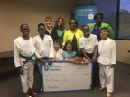 The Amerigroup Foundation grant was presented by (R-L) Tiffany Brailey and Reva Witherspoon to BridgingApps team members Cristen Reat and Cathy Foreman during Easter Seals Greater Houston's karate and yoga play group. Easter Seals of Greater Houston karate and yoga play group participants include Dylan Lewis, Dustin Lewis, Will Ellery, Maddy Reichard, Olivia Reichard, Jonah Moore, and Eli Ellery. (Photo: Business Wire)