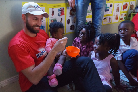 Kraft Heinz employee Evandro Patricio (left) from Auckland, New Zealand, visited two local crèches Sunday in Cape Town as part of a company sponsored meal-distribution trip. There, employees were able to meet with beneficiaries of the Kraft Heinz Micronutrient Campaign. Kraft Heinz recently announced its commitment to donate 1 billion meals worldwide by 2021 in collaboration with non-profit partners such as Rise Against Hunger (formerly Stop Hunger Now), which facilitated the trip. Photo Courtesy of Kraft Heinz.