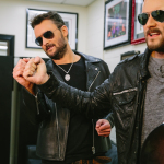 Eric Church compares features to his brand-new wax figure for Madame Tussauds Nashville. (Photo: Business Wire)