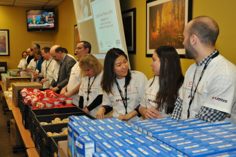 Harris Corporation employees in Clifton, New Jersey, help assemble food packs as part of a company-s ...