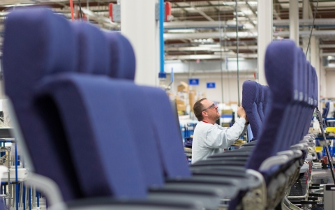 An employee from Rockwell Collins' new Interior Systems business building airline cabin seats at its ...