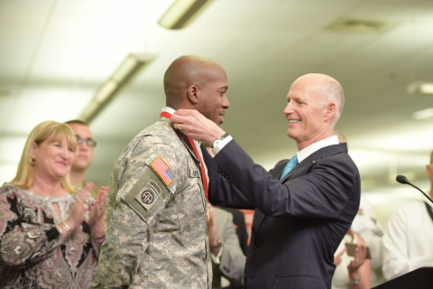 Florida Governor Rick Scott presents Jeffrey Clement, Comcast technician and member of the U.S. Army Reserves, with the Governor's Veterans Service Award. (Photo: Business Wire)
