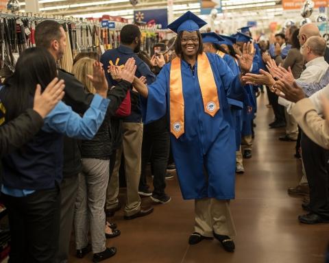 A Walmart associate receives high fives as she enters an academy graduation. (Photo: Business Wire)