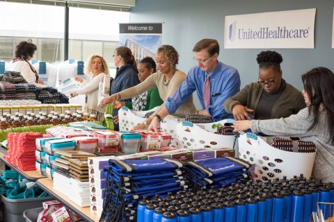Michael McGuire (center), CEO of UnitedHealthcare in New York, helps local employees assemble welcom ...