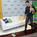 Pet Vet Dr. Evan Antin demonstrates one of the key adulting moments of new pet ownership - cleaning - while using a Swiffer Sweeper and holding an adoptable puppy from Bideawee Animal Shelter, Wednesday, April 26, 2017, in New York. (Photo by Diane Bondareff/Invision for Swiffer/AP Images)