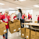 """At The Kraft Heinz Company offices in Chicago, kids and parents participated in a meal-packaging event Thursday put on by Rise Against Hunger, an international nonprofit that distributes food and aid to vulnerable populations around the world. The event was part of the company's first-ever """"Take Your Sons & Daughters To Work Day."""" Packages are scheduled to arrive in Zambia where a local nonprofit partner will distribute the meals to hungry children. (Photo: Business Wire)"""