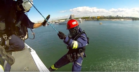 Miami Dade Fire Rescue Hazmat team rapells from a helicopter to a cargo ship connex box during joint drill with US Army wearing Demron ICE suits simulating a hazmat incident (Photo: Business Wire)