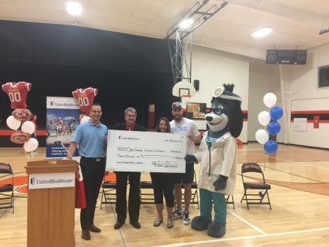 """Michael Margherio of UnitedHealthcare (left) presents a $20,000 check on behalf of Kansas City Chiefs tight end Travis Kelce to Oak Grove School District Superintendent Freddie Doherty (second from left) and Oak Grove Elementary School Principal Peggy Tiffany (center), along with UnitedHealthcare mascot Health E. Hound (right). Kelce (second from right) helped the school refinish its gymnasium floor and fund the district's """"snack packs"""" program through his Dreambuilders Foundation. Following the dedication ceremony, Kelce inaugurated the new gym by hosting a relay race for students (Photo: Garrett Kasper/UnitedHealthcare)."""