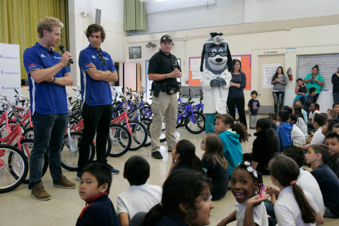 UnitedHealthcare Pro Cycling Team members Daniel Eaton (left) and Tanner Putt joined Sacramento Sheriff's Activities League Deputy Joe Gordon and UnitedHealthcare mascot Dr. Health E. Hound at Pacific Elementary in Sacramento, Calif., today to distribute 50 bike helmets and 50 bikes. The bikes and helmets were donated by UnitedHealthcare in advance of the Amgen Tour of California (Photo:Gary Fong).