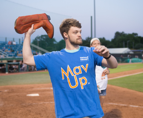 UTA Mavericks fan, Cade Olson, attempted to toss a cowboy boot into a barrel for a chance to win $50,000. (Photo: Business Wire)