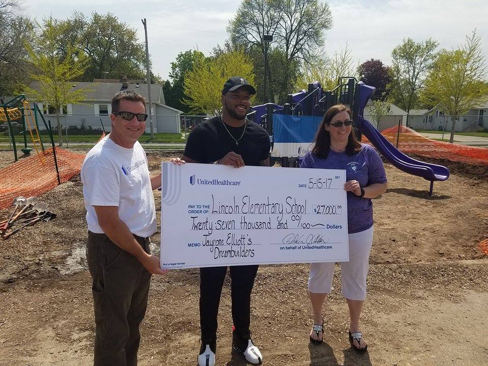 Dustin Hinton, CEO and president, UnitedHealthcare of Wisconsin, Jayrone Elliott, Green Bay Packers linebacker, and Angela Hager, principal of Lincoln Elementary School, announced UnitedHealthcare's $27,000 donation to Elliott's Dreambuilders program at Lincoln Elementary School in Green Bay. The donation was used for a new playground at the school installed by UnitedHealthcare volunteers on Monday (Photo courtesy of UnitedHealthcare).