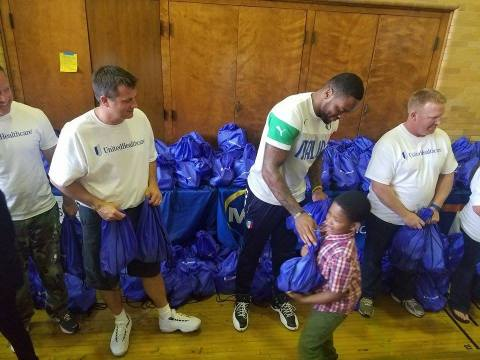 Students from Milwaukee's Townsend Street School received backpacks filled with food on Tuesday from Green Bay Packers linebacker Jayrone Elliott and Dustin Hinton (left), CEO and president, UnitedHealthcare of Wisconsin. UnitedHealthcare donated $11,000 to Elliott's Dreambuilders program. The donation will be used to fund Blessings in a Backpack, a national nonprofit that provides students with bags of nutritious food each weekend (Photo courtesy of UnitedHealthcare).