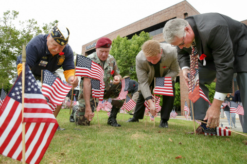 Left to right: Andy Timko of the American Legion, Don Collins of the 82nd Airborne Division Assoc. Honor Guard, UnitedHealthcare employee Allen Patrick, and UnitedHealthcare of California CEO Robert Falkenberg honor America's veterans and service members this Memorial Day by placing more than 1,800 flags in front of UnitedHealthcare Orange County offices. Employees were joined by members of American Legion Cypress Post 295 who shared their personal stories and also placed the flags in front of the building (Photo: Jamie Rector).