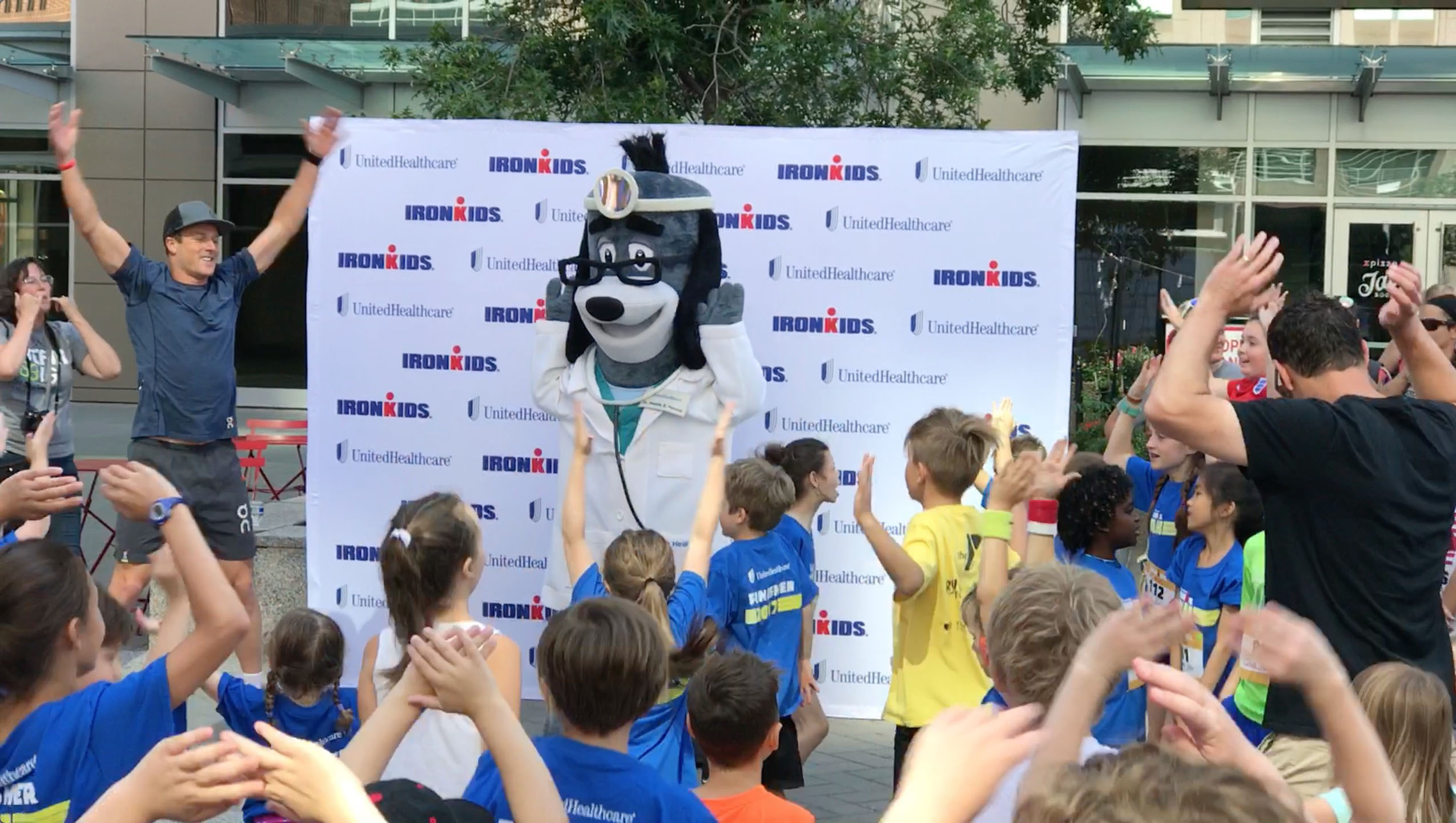 Leon Griffin, an IRONMAN pro-athlete from Australia, and UnitedHealthcare mascot Dr. Health E. Hound led warm-ups prior to today's UnitedHealthcare IRONKIDS Raleigh Fun Run at Raleigh Marriott City Center. Derek K. Harris Jr. of UnitedHealthcare and state Rep. Duane Hall gave medals to more than 160 kids as they crossed the finish line. (Photo credit: Marc Kawanishi)