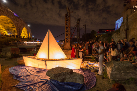 Blessing of the Boats invited Northern Spark goers to take an artist-led journey with a small group of people. On the way visitors experienced stories, singing, and silence and had the opportunity to set their own story and message afloat in a folded paper boat along the shores of the Mississippi River. This installation showcased the growing refugee crisis currently occurring in Europe and Northern Africa and its relationship to climate change. Photo provided by Northern Spark 2016.