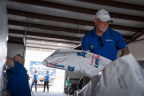 Sean Cuddeback, Store Leader of a Colorado Springs, Colo., PetSmart store, helps unload a semi-truck full of 250,000 pet food meals for dogs and cats in need at Rescue Bank affiliate, St. Paws, and adjacent shelter, National Mill Dog Rescue in Peyton, Colo., a suburb of Colorado Springs, Colo. PetSmart just announced its initial shipments - three semi-truck loads of donated pet food - delivered in the past few days as part of nearly 90 semi-truck loads to be donated this summer from PetSmart's Buy a Bag, Give a Meal program, where the retailer is giving a meal to a pet in need for any and every bag of dog or cat food purchased through Dec. 31, 2017, in its more than 1,500 stores and online at PetSmart.com and PetSmart.ca. Through this historic philanthropic program, PetSmart expects to donate more than 60 million meals to pets in need with semi-truck deliveries of donated pet food throughout 2017 and well into 2018. With PetSmart Charities and its partners Feeding America and Rescue Bank, the much-needed food will land at hundreds of locations across North America including local shelters and rescues, as well as to food banks and pantries where pet food is a rare offering. (Photo: Business Wire)