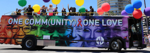 """AHF's """"One Community, One Love"""" custom-wrapped bus is scheduled to appear in Pride parades in U.S. cities including Brooklyn (6/10); Long Island (6/11); Washington, DC (6/10); Columbus, OH (6/17); Houston (6/24); New York City, NY (6/25); San Diego (7/15); Oakland, CA (9/10); Dallas (9/16); Atlanta, GA (10/14); and Las Vegas (10/20). (Photo: Business Wire)"""