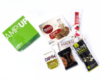 JetBlue's new AmpUp box: These healthful nibbles hit the trifecta of gluten-free, vegan and kosher, offering Mary's Gone Crackers®, red pepper hummus, a MadeGood® chocolate crispy rice square, Greek olives, roasted almonds and a That's It® fruit bar. (Photo: Business Wire)