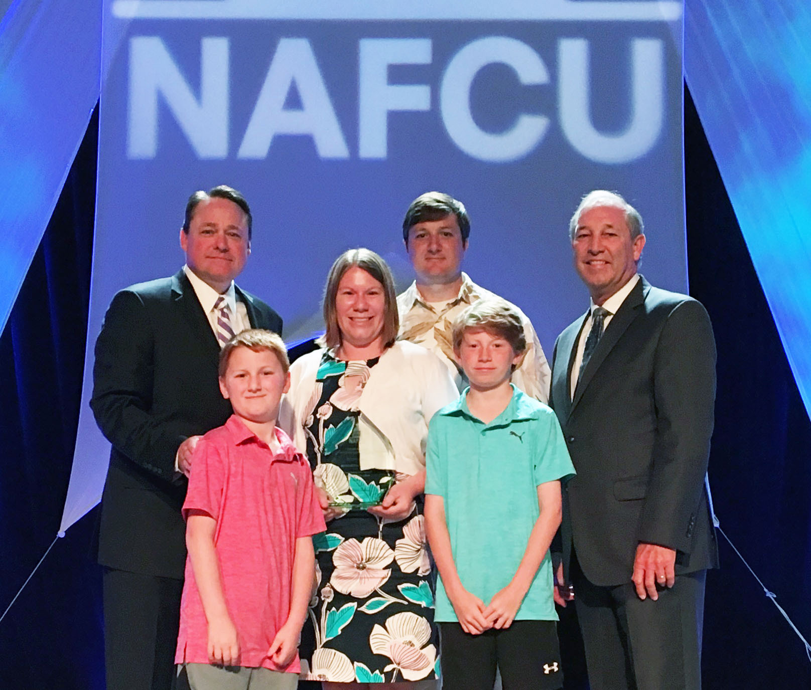 Northwest Federal's Harmonie Taddeo presented with NAFCU's Professional of the Year Award. Left to right: Dan Berger, President and CEO of NAFCU; Harmonie Taddeo and family; Charles A. Rutan NAFCU's Director-at-Large. (Photo: Business Wire)