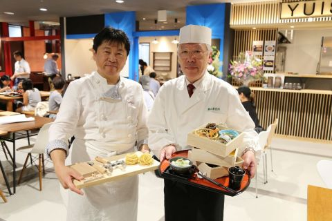 """In front of the """"Tsuruoka Bar,"""" that is consisted of a restaurant that serves local delicacies, a sushi restaurant that serves sushi with freshly caught fish, a Spanish-style bar, and a wine/Japanese Sake bar. Chef Masayuki Okuda (Left) from """"Farinamore,"""" a pasta and dolce restaurant and Head Chef Mr. Masatomi Toki (Right) from """"Ayatsuru,"""" a restaurant that serves local Tsuruoka cuisines. (Photo: Business Wire)"""