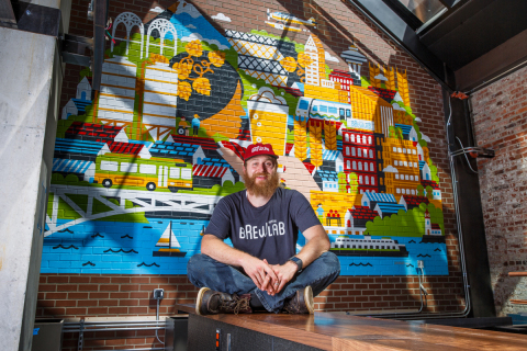 Head Brewer Nick Crandall sits in front of Redhook Brewlab's custom mural, designed by Grammy-nominated Seattle illustrator and Sub Pop Records art director Sasha Barr. (Photo: Business Wire)
