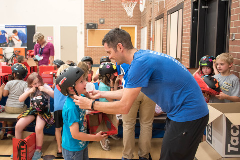 Six-year-old Cole Deyling receives a bike helmet from UnitedHealthcare Pro Cyclist Greg Henderson at a bike and helmet safety event at Hawthorne Elementary School in Boise, Idaho. UnitedHealthcare Pro Cyclists encouraged kids from the Boys & Girls club to be safe, stay active and participate in the upcoming Downtown Boise Twilight Criterium Kids' ride event (Photo: Chad Case).